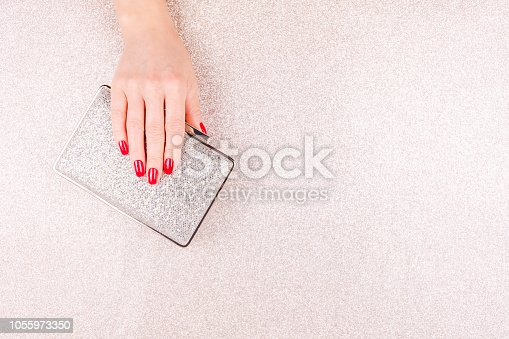 istock Woman hand with red manicure holding a small golden evening clutch. Holiday, party and celebration concept 1055973350