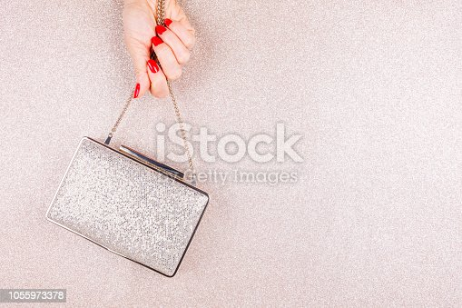 istock Woman hand with red manicure holding a small golden evening clutch. Holiday, party and celebration concept 1055973378