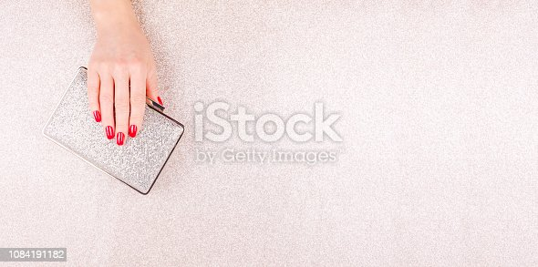 istock Woman hand with red manicure holding a small golden evening clutch. Holiday, party and celebration concept 1084191182