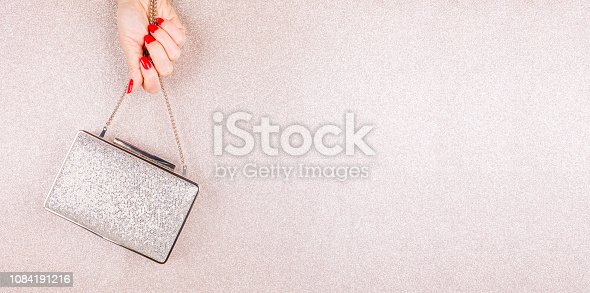 istock Woman hand with red manicure holding a small golden evening clutch. Holiday, party and celebration concept 1084191216