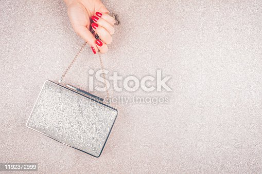 istock Woman hand with red manicure holding a small golden evening clutch. Holiday, party and celebration concept 1192372999
