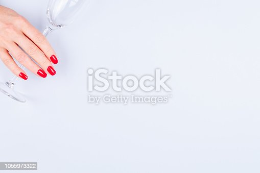 istock Woman hand with red manicure holding champagne glass. Holiday, party and celebration concept 1055973322