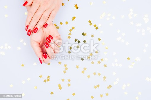 istock Woman hand with red manicure on blue background with sprinkles. Holiday, party and celebration concept 1055973360