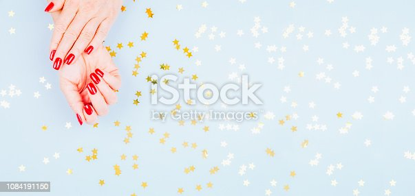 istock Woman hand with red manicure on blue background with sprinkles. Holiday, party and celebration concept 1084191150