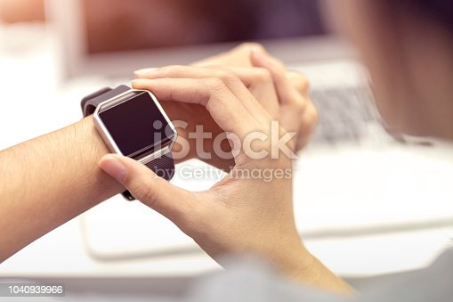 Woman hand with smart watch on wrist, wearable watch and technology computer laptop for communication, checking time.