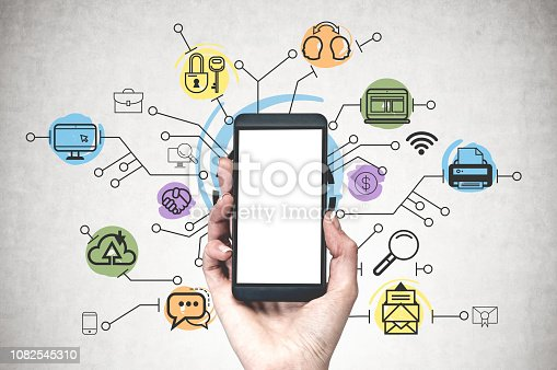 Woman hand holding smartphone with mock up screen over concrete wall background with colorful computer and internet icons on it.
