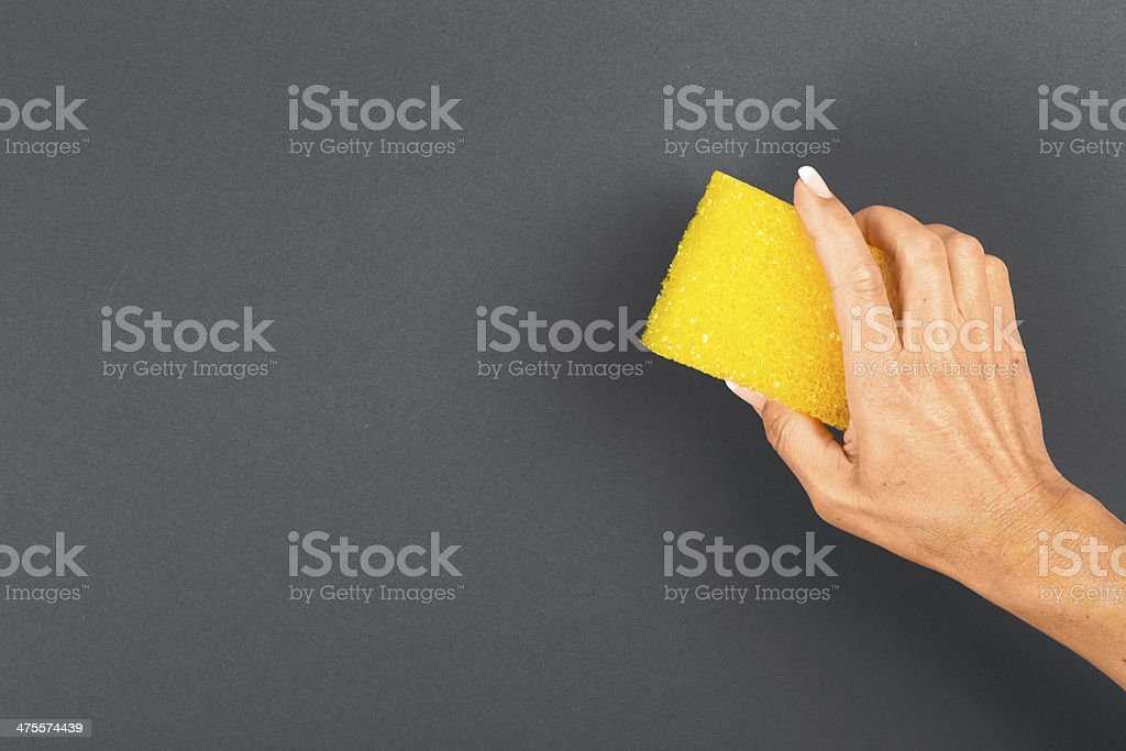 Woman hand with sponge on blank Blackboard stock photo