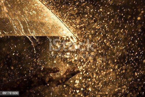 691761646istockphoto Woman hand with umbrella in the rain 691761630