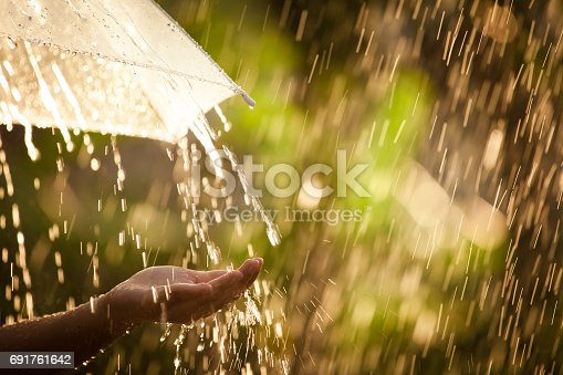 691761646istockphoto Woman hand with umbrella in the rain 691761642