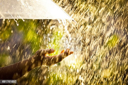 691761646istockphoto Woman hand with umbrella in the rain 691761652