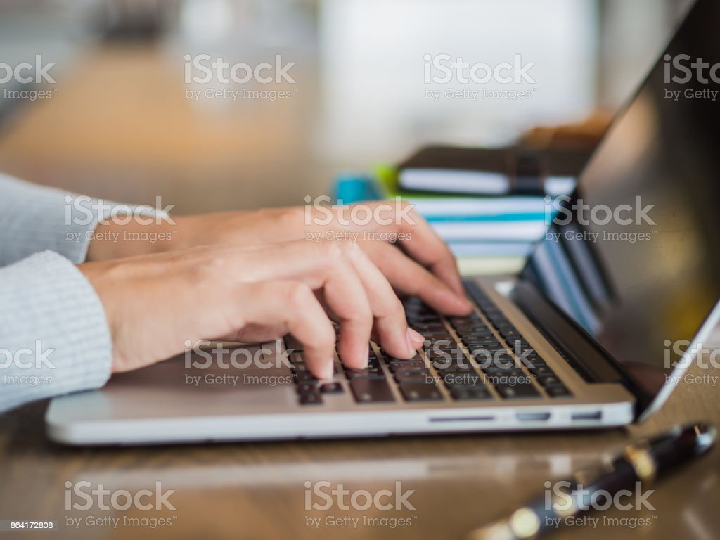 Woman hand working on her laptop with selective focus. Social networking technology concept. royalty-free stock photo