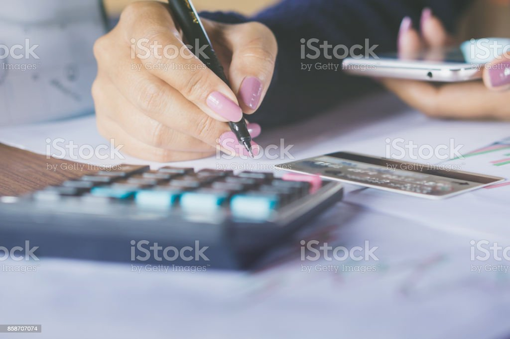 woman hand writing and calculating her monthly expenses with blur background credit card hand holding smart phone stock photo