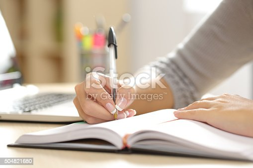 istock Woman hand writing in an agenda at home 504821680