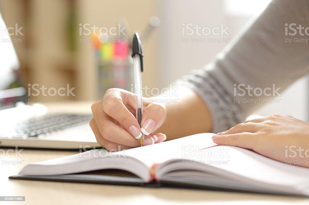 Mano de mujer escribiendo en un orden del día en su - foto de stock