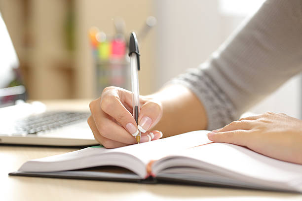 woman hand writing in an agenda at home - writing class stock photos and pictures