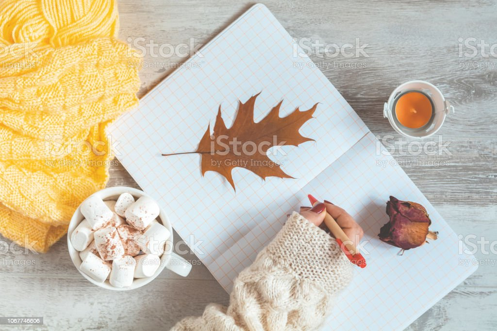 Woman hand writing in notepad, cup of coffee, dried rose, candle and autumn leaf stock photo