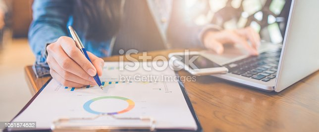 Woman hand writing on charts and graphs that show results with a pen and using a laptop computer working in the office.Web banner.