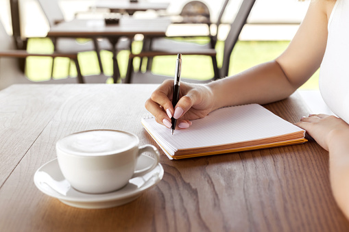 Woman hand writing on notebook in the cafe