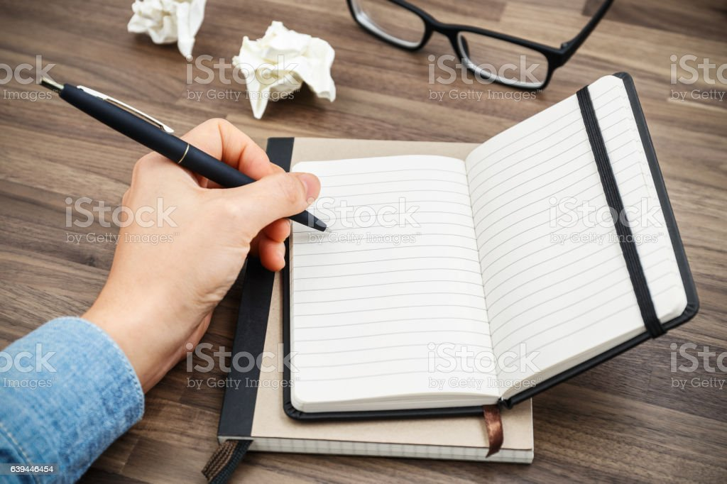Woman hand writing on notebook Woman hand writing on notebook on wood desk with crumpled paper balls Adult Stock Photo