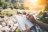 istock Woman hand writing on notebook with pencil at river background. 1301757934