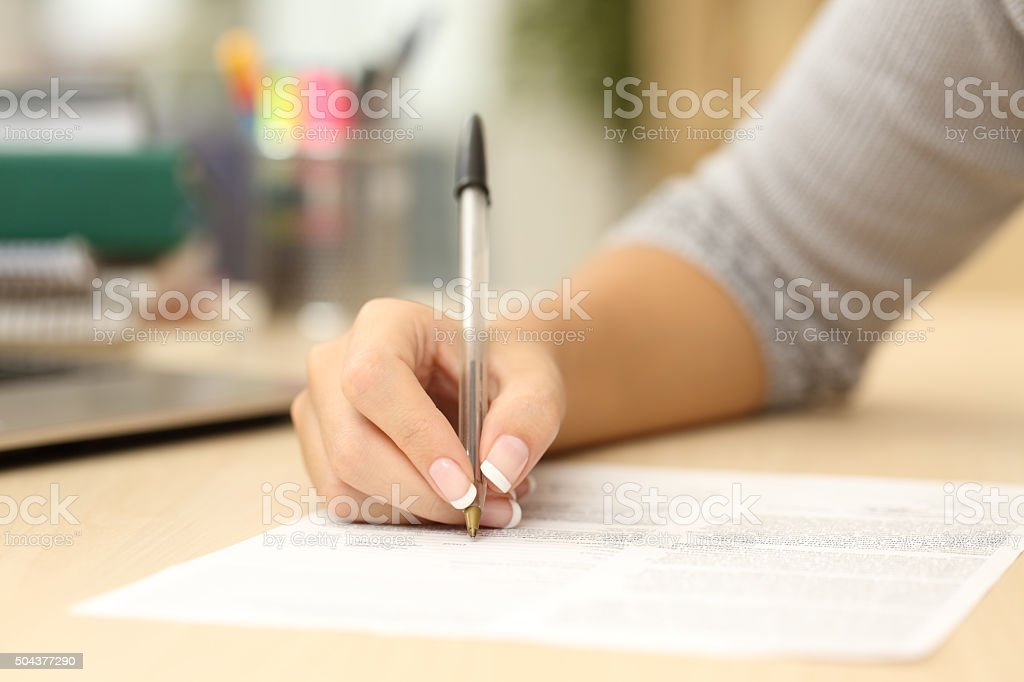 Woman hand writing or signing in a document stock photo