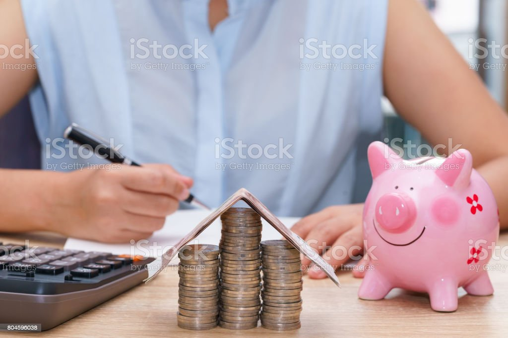 Woman hand writing with pink piggy bank on wooden desk - save money to buy house concept. stock photo