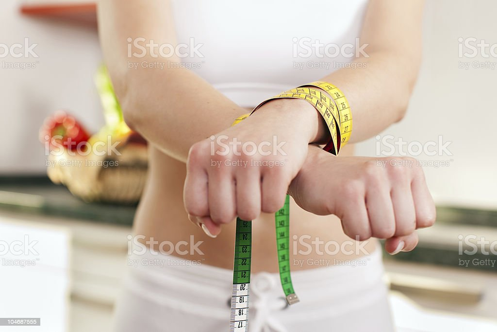 Woman handcuffed to measuring tape representing wild diet stock photo