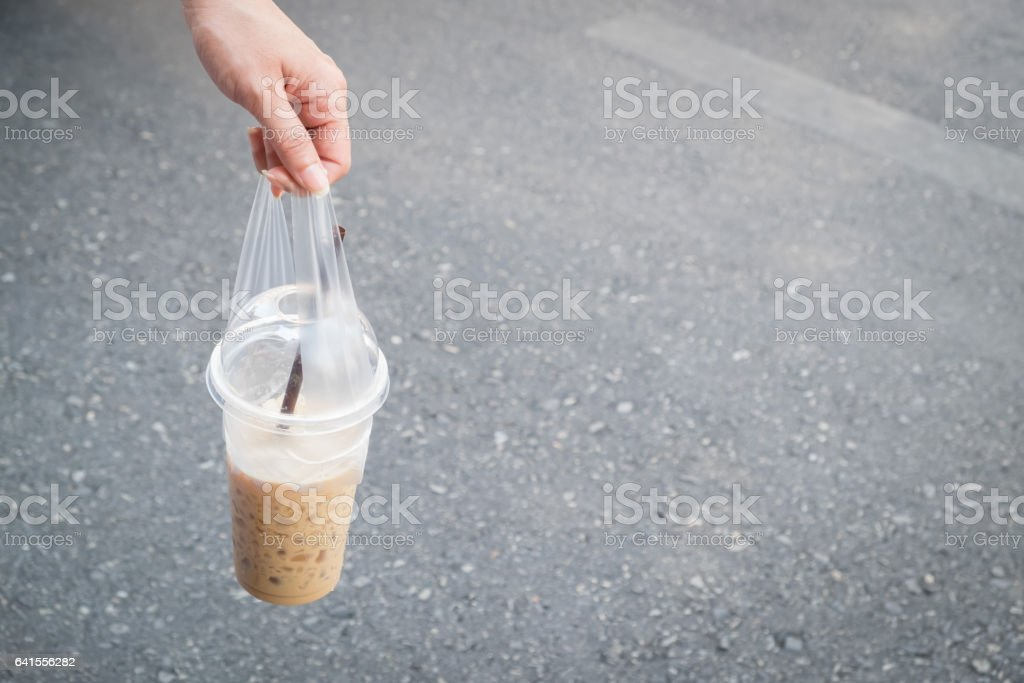 Woman handing a cup of cool coffee with blurred the road. stock photo