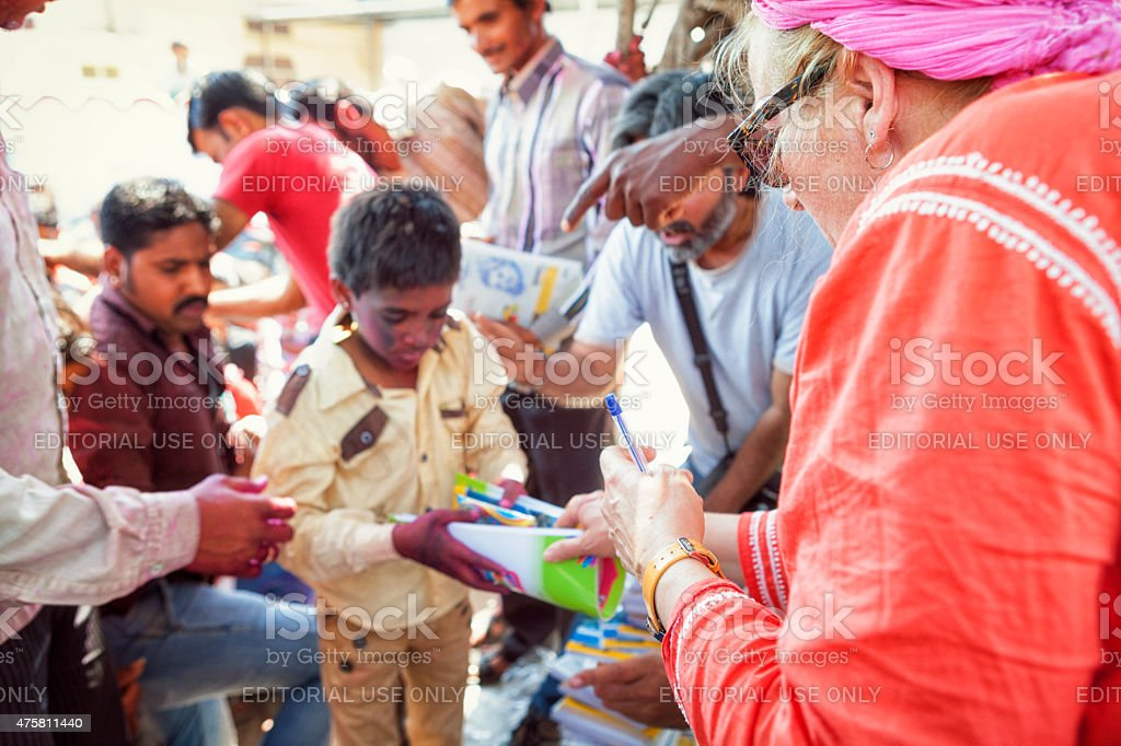 Woman handing out school supplies to children in rural India stock photo