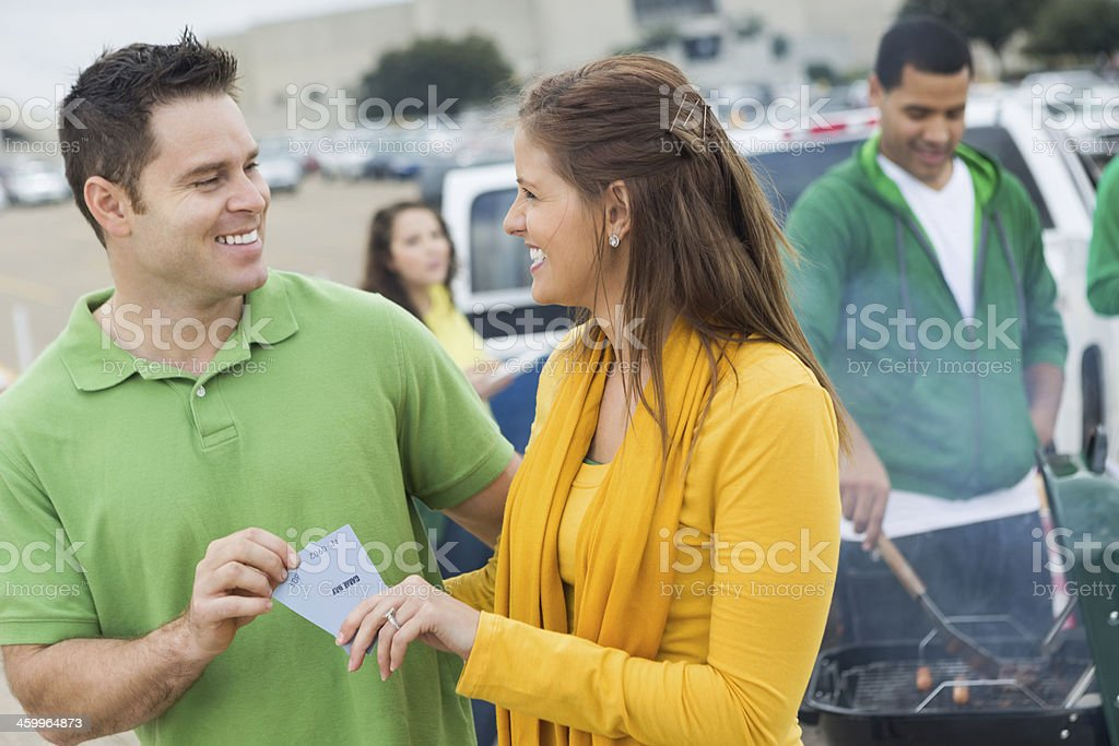 Woman Handing Tickets to Man at Tailgate Party stock photo