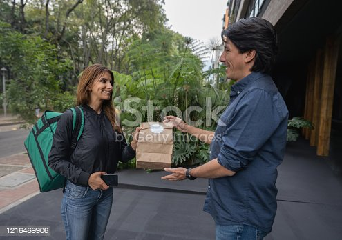 Latin American woman handling a delivery to a happy customer