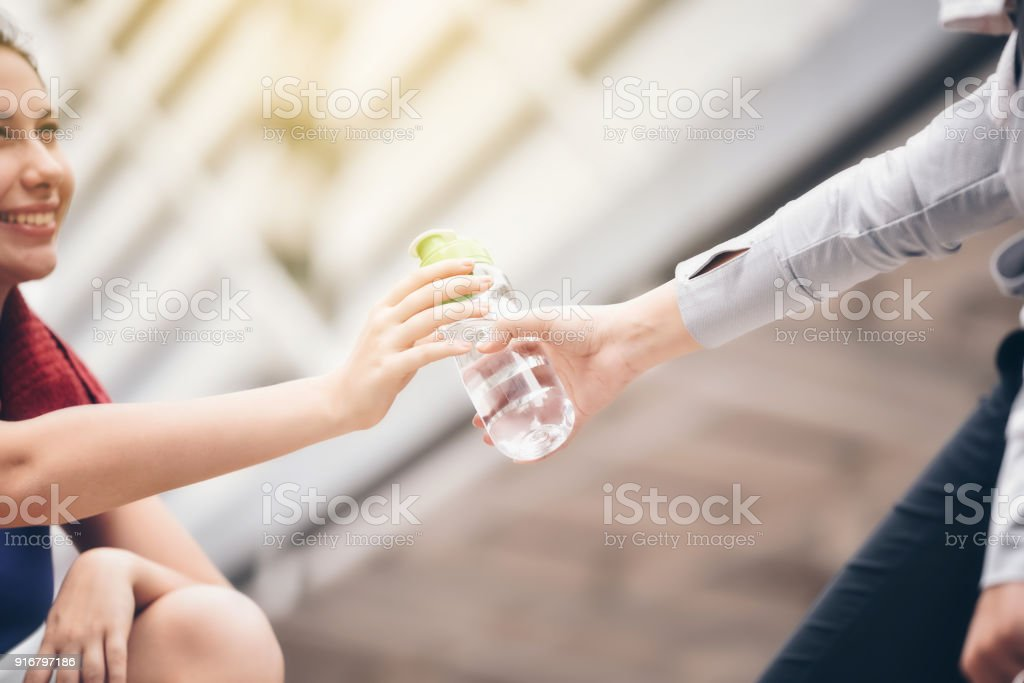 Eine Frau reicht eine Flasche kühlen Trinkwasser zu ihrer Freundin nach dem Training. – Foto