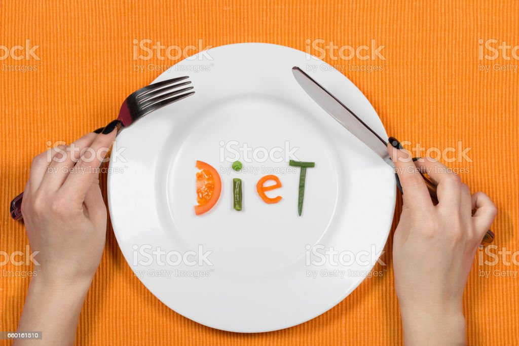 Woman hands above the plate with word diet made of pieces of vegetables. stock photo