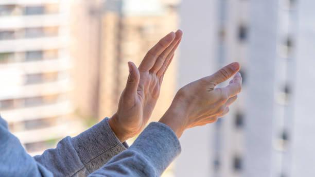 Frau Hände applaudieren medizinisches Personal von ihrem Balkon. Menschen in Spanien klatschen Dankbarkeit auf Balkonen und Fenstern zur Unterstützung von Gesundheitspersonal, Ärzten und Krankenschwestern während der Coronavirus-Pandemie – Foto