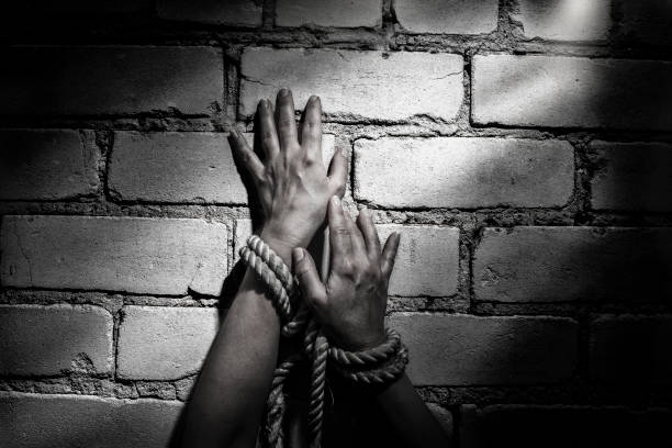 woman hands bound prisoner in room,hands bound woman hands bound prisoner in room,hands bound human trafficking stock pictures, royalty-free photos & images