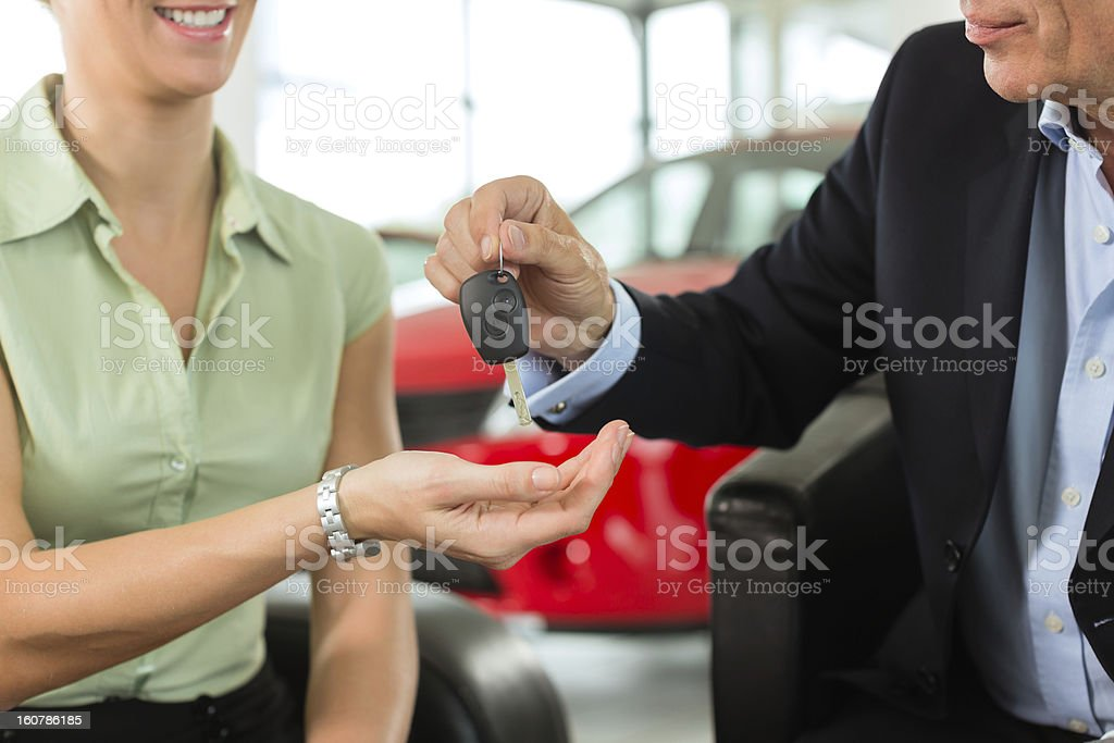 Woman hands car keys to man at auto dealer stock photo