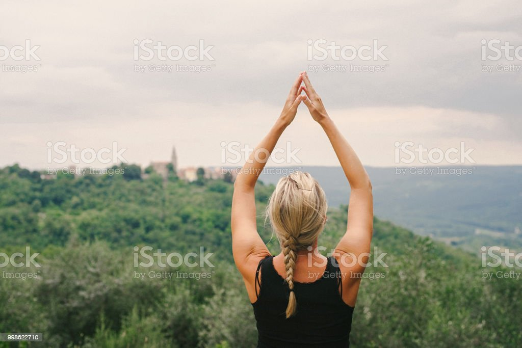 Woman hands clasped in namaste above head yoga pose stock photo