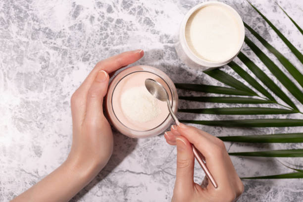 Woman hands, collagen powder and smoothie. Woman pour collagen powder or protein in morning smoothie or yogurt. Natural beauty and health supplement. Healthy lifestyle. Flatlay, top view. Copy space. peptide stock pictures, royalty-free photos & images