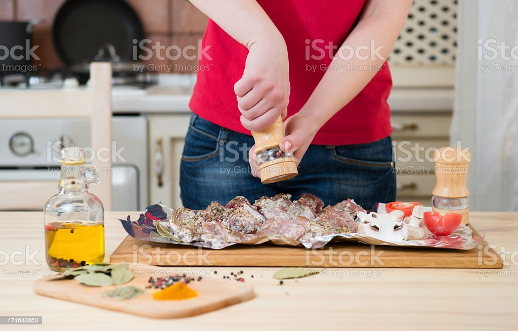 Woman hands cooking at home kitchen. Girl peppers meat. royalty-free stock photo