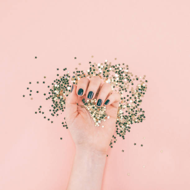 mulher mãos cobertas de confetes de estrelas douradas sobre pink - manicure - fotografias e filmes do acervo