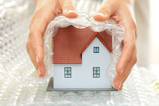 Woman hands covering a model house with bubble wrap stock photo