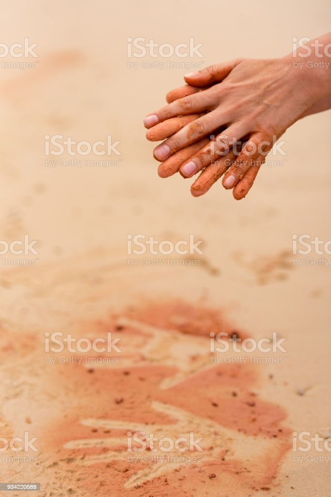 Woman hands creating shapes with red sand on the beach in aboriginal art style stock photo