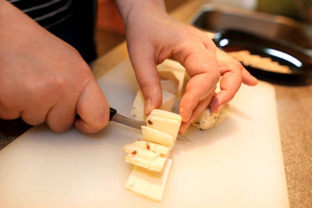 Woman hands cutting piece of cheese, she prepare food at kitchen. Chef cutting cheese with knife on wooden board on restaurant kitchen table. Housewife with a knife sliced cheese on cutting board. stock photo
