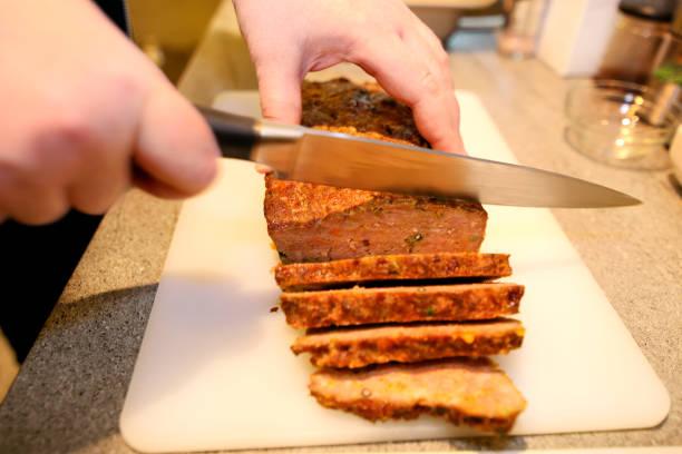Mulher cortando o pedaço de bolo de carne, ela preparem para degustação de comida na cozinha. Chef bolo de carne corte com faca a bordo na mesa de cozinha de restaurante. Dona de casa em fatias de carne na tábua. - foto de acervo