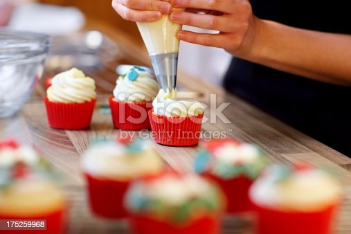 Woman hands decorating cupcakes using a pastry bag with frosting