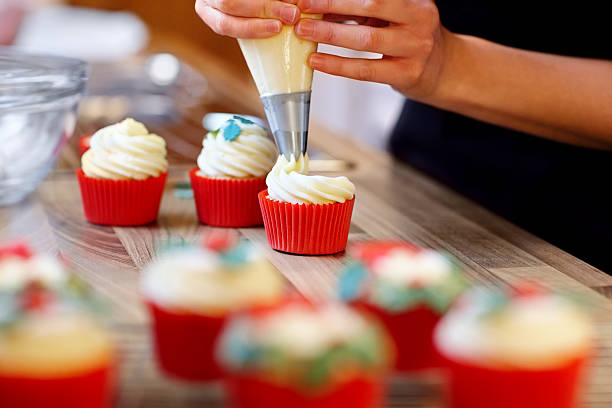 Woman hands decorating cupcakes Woman hands decorating cupcakes using a pastry bag with frosting decorating a cake stock pictures, royalty-free photos & images