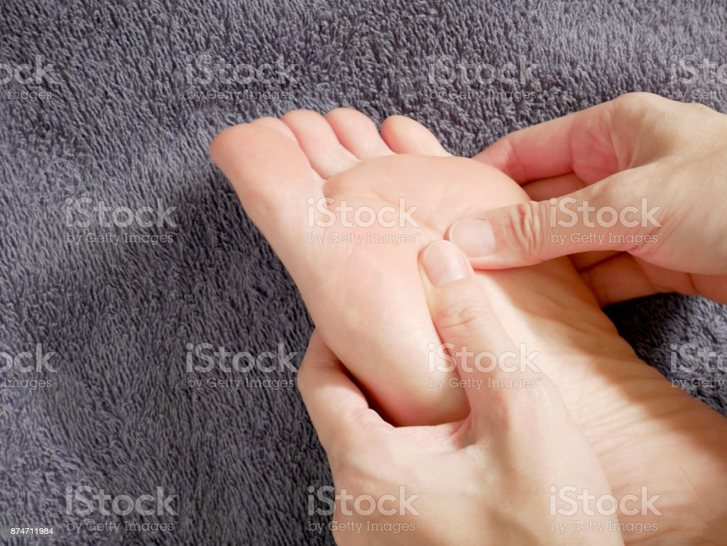 Woman hands doing foot massage stock photo