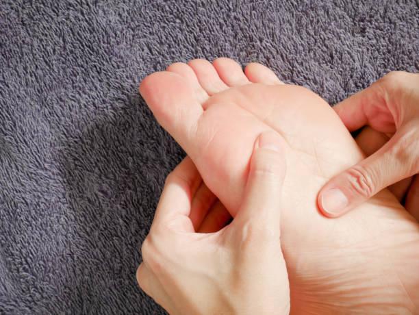 Woman hands doing foot massage stock photo