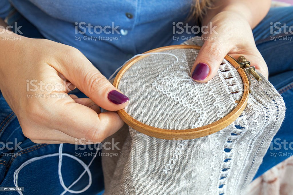 Woman hands doing openwork embroidery on homespun linen. stock photo