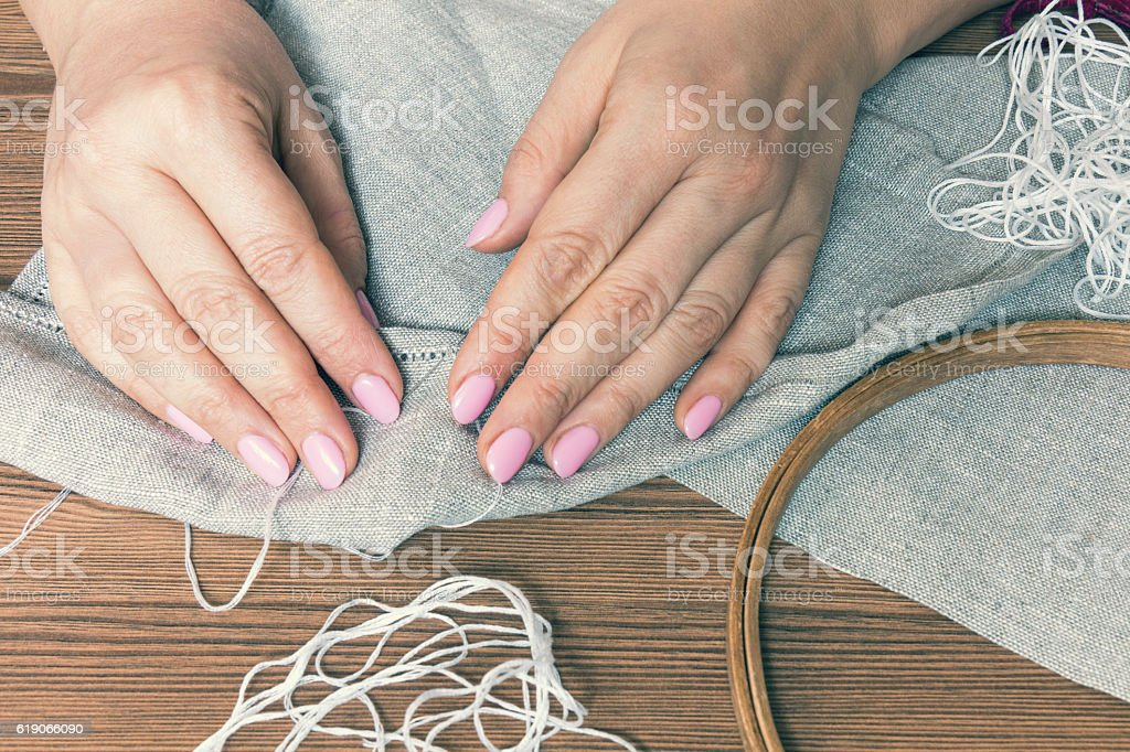 Woman hands doing openwork embroidery stock photo
